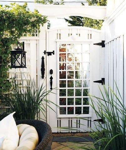 Mirror on White Garden Gate with Lattice via Style at Home | Photo by Michael Graydon