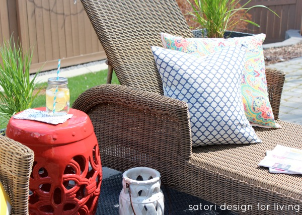Outdoor Living Space with Wicker Chaise Lounge, Red Garden Stool and Blue Pillow - Satori Design for Living