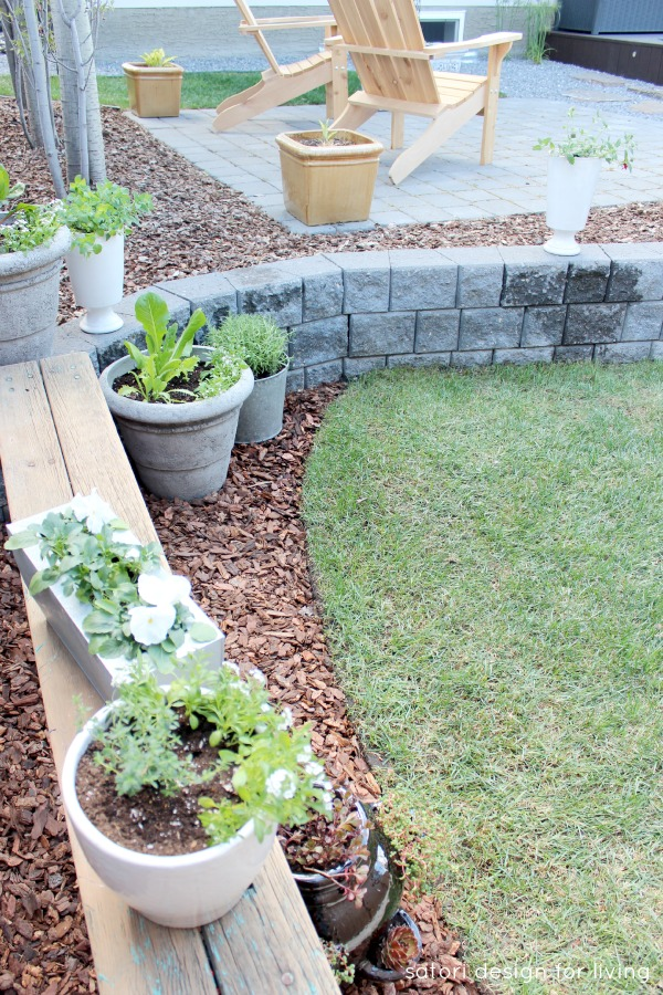 Grey stone retaining wall with rustic bench and container garden | Satori Design for Living