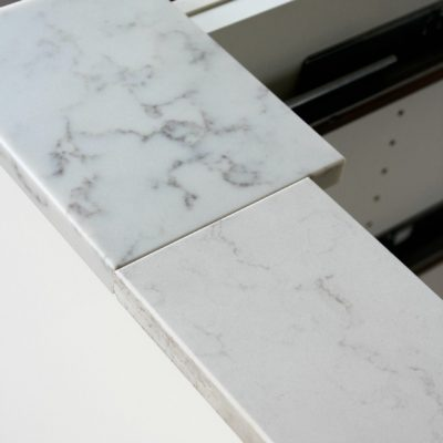 Considering installing a marble quartz countertop in your kitchen? Take a look at the options we've narrowed it down to for our kitchen with white cabinets.