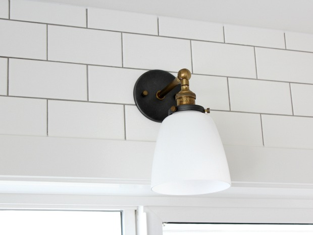 Aged Brass Sconce with Milk Glass Cloche Shade - White Subway Tile with Pewter Grout Around the Kitchen Sink Window